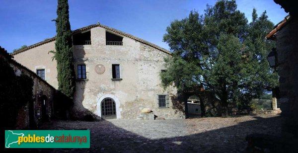 Panormàmica de la façana de la Masia de Can Deu, des de la porta d'entrada al pati